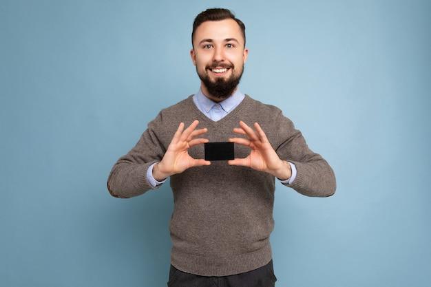 Cool sorridente bruna uomo barbuto che indossa un maglione grigio e camicia blu isolato sulla parete di fondo che tiene la carta di credito che guarda l'obbiettivo.