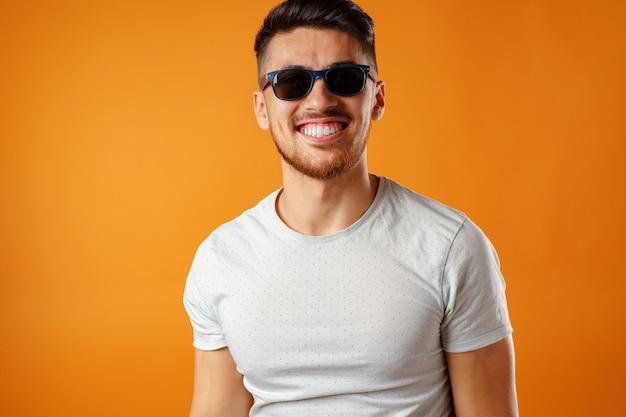Cool ragazzo sorridente in occhiali da sole neri e camicia bianca