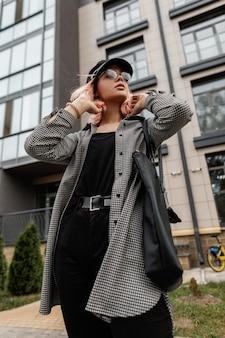 Una bella donna elegante e alla moda con gli occhiali e un berretto vintage in jeans alla moda casual con una borsa cammina nella città vicino all'edificio