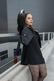 Elegante modello di donna hipster alla moda in abito nero alla moda con giacca di pelle nera e vestito con gambe sexy in collant e posa in città