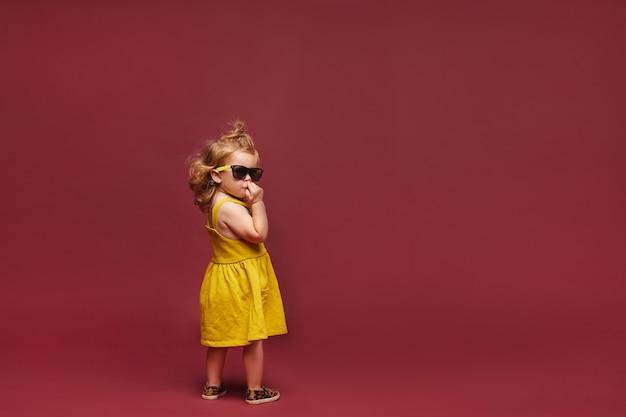 Raffreddi la bambina alla moda in vestito giallo e occhiali da sole ed occhiali da sole isolati ai precedenti rosa. moda bambino. copia spazio