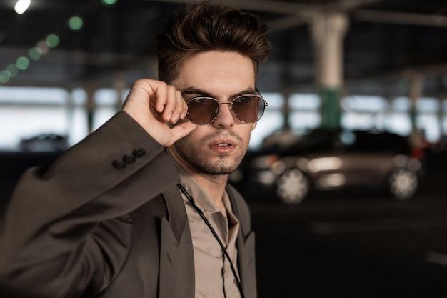 Il bel ritratto alla moda di un bel giovane con un'acconciatura in abiti alla moda guarda con occhiali da sole vintage passeggiate in città