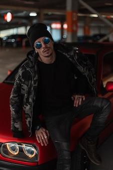 Cool giovane hipster alla moda con occhiali da sole blu alla moda in abbigliamento casual con giacca militare invernale, pullover e cappello vicino all'auto rossa in città