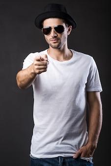 Fresco e alla moda. bel giovane con occhiali da sole e fedora che tiene le mani in tasca mentre sta in piedi su sfondo nero