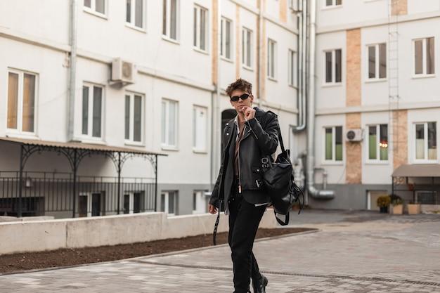 Fresco hipster alla moda giovane in occhiali da sole in una giacca di pelle nera alla moda oversize con zaino con una sigaretta posa vicino agli edifici in una città. il ragazzo moderno serio fuma in strada.