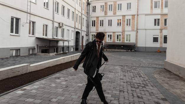 Fresco hipster alla moda giovane in occhiali da sole in una giacca di pelle nera alla moda oversize con un'acconciatura alla moda con zaino posa vicino agli edifici in una città. il ragazzo moderno serio cammina nella strada