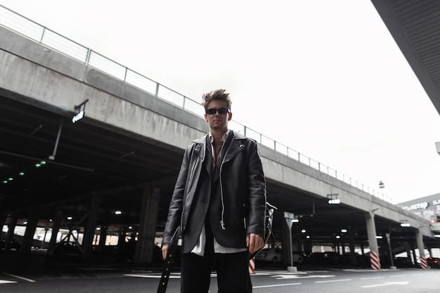 Fresco hipster alla moda giovane in occhiali da sole in una giacca di pelle nera alla moda oversize giovanile con un'acconciatura alla moda si trova vicino a un edificio vintage in una città. ragazzo moderno serio in strada.