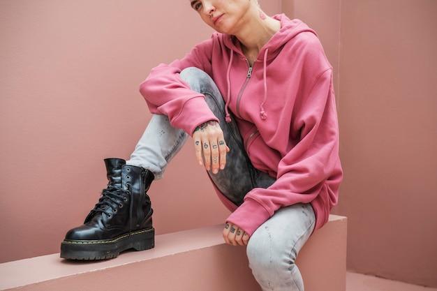 Bella donna con una giacca con cappuccio rosa e un combattimento nero