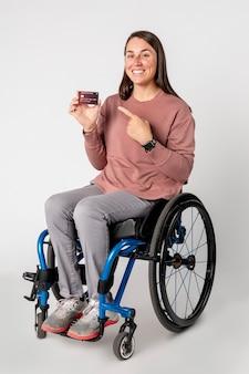 Bella donna su una sedia a rotelle che mostra una carta di credito premium