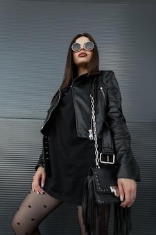 Modello di donna cool giovane moda hipster con occhiali da sole rotondi vintage in una giacca di pelle nera alla moda e abito nero con un'elegante borsa si trova vicino a un edificio moderno sulla strada