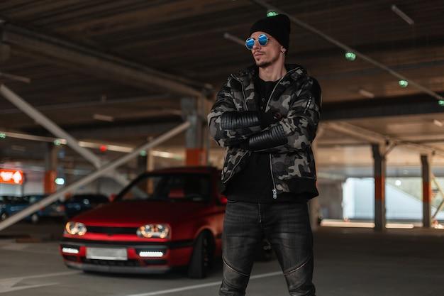 Un giovane modello cool con occhiali da sole eleganti e cappello nero in giacca militare invernale alla moda cammina per strada