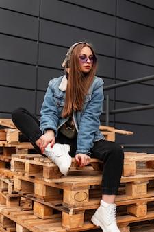 Cool giovane donna alla moda hipster in abiti casual alla moda per giovani in posa di occhiali viola alla moda in città. la modella americana sexy ragazza affascinante si siede su pallet di legno in strada. stile.