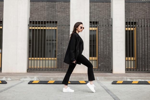 Bella giovane donna in occhiali da sole alla moda in abiti casual neri alla moda in scarpe da ginnastica in pelle bianche alla moda cammina vicino a un edificio moderno. attraente ragazza europea in abbigliamento casual giovanile viaggia in città.