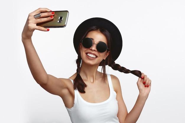 Cool giovane donna che spara selfie sulla fotocamera frontale isolata sul muro bianco