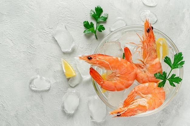 Gamberi raffreddati in una ciotola con ghiaccio, limone e prezzemolo su sfondo grigio. cibo italiano, copia dello spazio.
