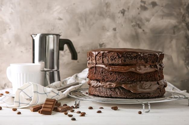 Rack di raffreddamento con una deliziosa torta al cioccolato sul tavolo