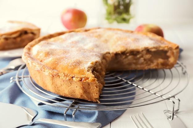 Griglia di raffreddamento con gustosa torta di mele appena sfornata sul tavolo