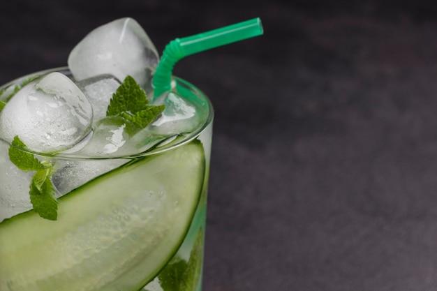 Bevanda estiva rinfrescante con ghiaccio e fette di cetriolo. menta e cetriolo tritato su sfondo nero. copia spazio