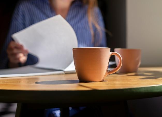Cooncept di prepararsi per l'esame leggendo il libro che studia il libro di testo nella caffetteria al moderno tavolo di legno