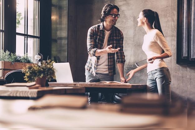 La cooperazione è la chiave del successo. fiducioso giovane uomo e donna che lavorano insieme e sorridono mentre si trovano vicino alla scrivania in ufficio creativo creative