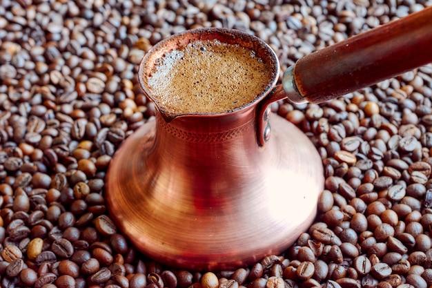 Il cezve di rame si erge sui chicchi di caffè