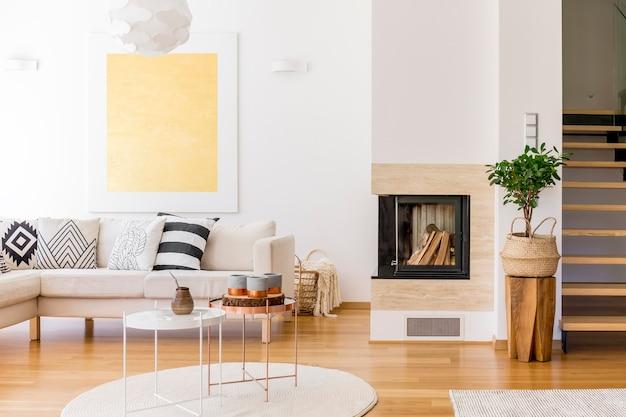 Tavolino da caffè in rame su tappeto bianco in soggiorno con camino e pittura dorata sul muro