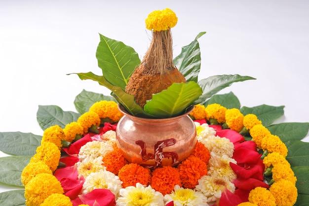 Kalash di rame con cocco, foglia e decorazione floreale su bianco