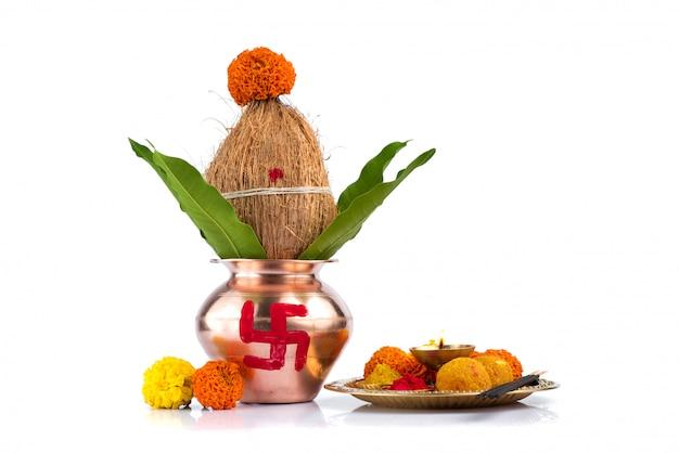 Kalash di rame con cocco e foglia di mango e pooja thali con diya, kumkum e dolci con decorazioni floreali su sfondo bianco. indispensabile in indù puja.