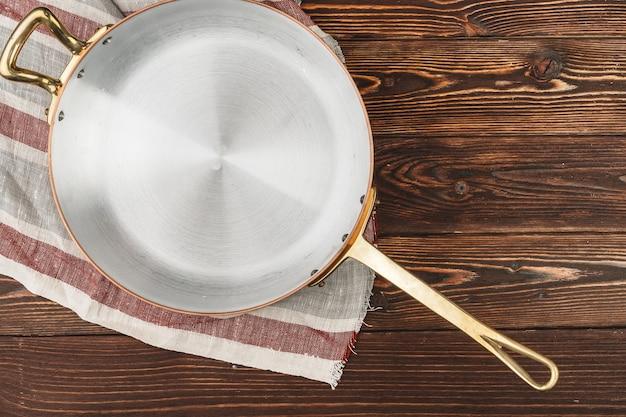 Pentola in rame con tovaglia a quadretti su tavola di legno