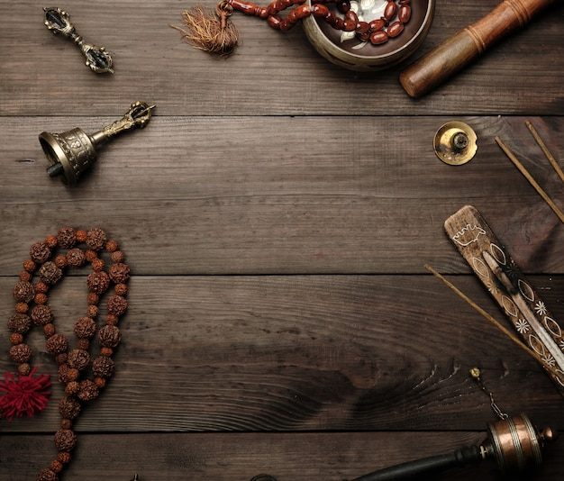 Ciotola di canto in rame, grani di preghiera, tamburo di preghiera e altri oggetti religiosi tibetani