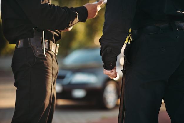 I poliziotti in uniforme controllano l'auto sulla strada