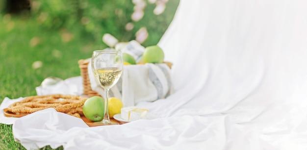 Copia spazio colazione all'alba, sul foglio bianco di erba con un vassoio con formaggio e vite, pane secco, mela, limone. umore romantico, concetto estetico di stile di vita lento, vista dall'alto