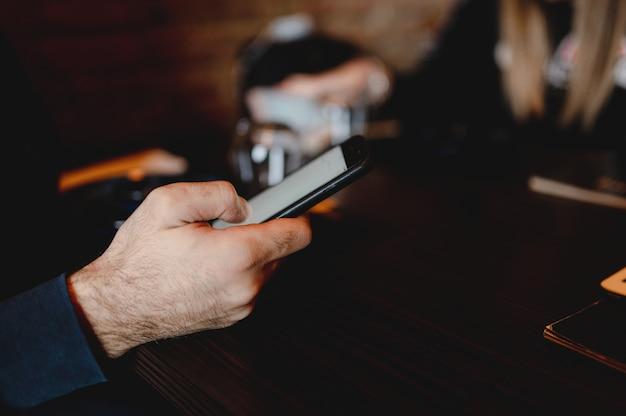 Copi la mano dell'uomo irriconoscibile del primo piano dello spazio che tiene uno smartphone che legge la carta del menu del cibo del ristorante in linea.