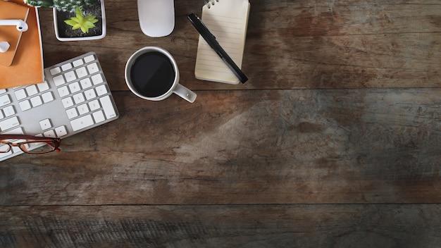 Copi lo spazio, la scrivania piana laica con la tazza del computer portatile, del taccuino, della matita, del cactus e di caffè sulla vecchia tavola di legno rustica.