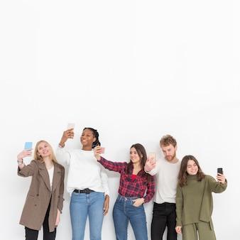 Amici di copia-spazio che fanno selfie