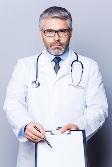 Copia spazio nei suoi appunti. medico maturo sicuro che guarda la macchina fotografica e indica lo spazio della copia sui suoi appunti mentre sta in piedi isolato su bianco