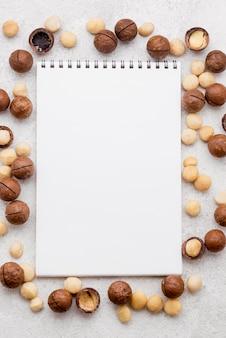 Copia il blocco note dello spazio sopra noci di macadamia in rotoli di cioccolato