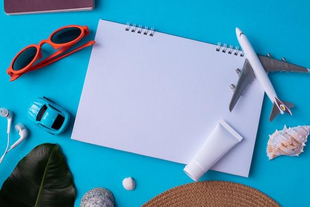 Copiare lo spazio sulla carta del blocco note con accessori da viaggio in estate.
