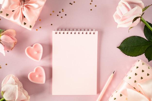 Copia il blocco note dello spazio per il tuo testo su un tavolo rosa chiaro con rose rosa e scatole regalo. laici piatta. vista dall'alto.