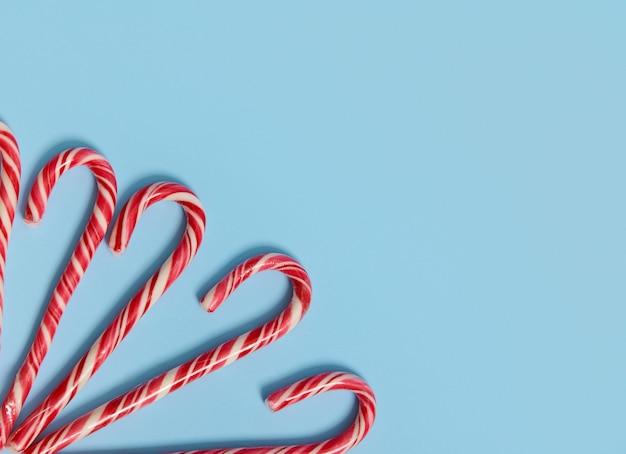 Copia spazio per testo e pubblicità su sfondo blu con dolci bastoncini di zucchero natalizi nell'angolo dell'immagine. veduta dall'alto della decorazione di natale.