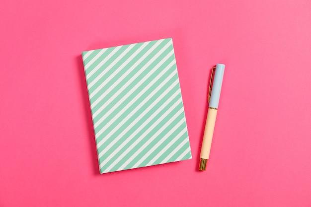 Quaderno e penna sul tavolo rosa