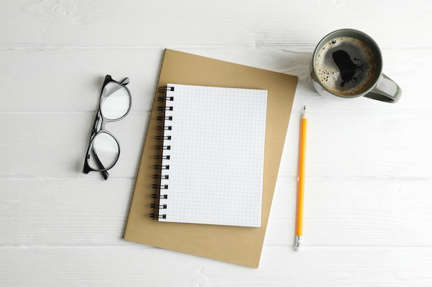 Quaderni, tazza di caffè, matite e bicchieri su spazio in legno, spazio per il testo