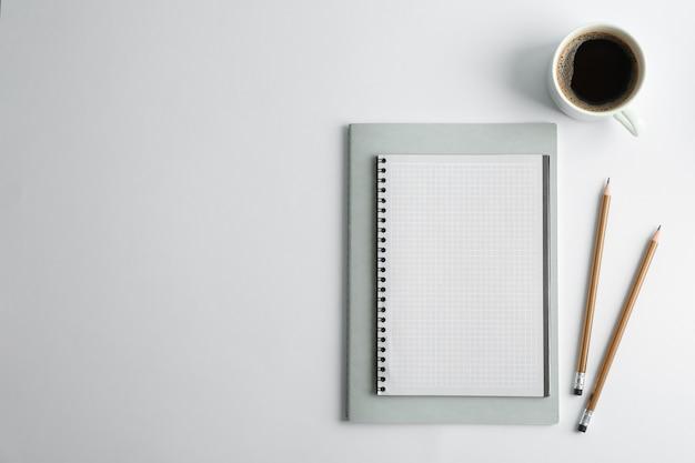 Spazio per quaderni, tazza di caffè e matite per il testo