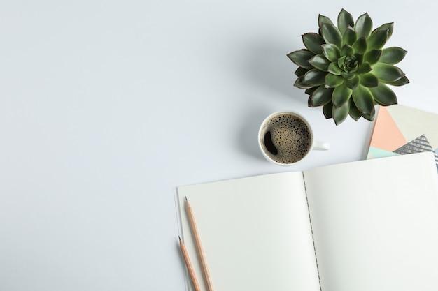 Quaderni, tazza di caffè, matite e spazio succulento per il testo