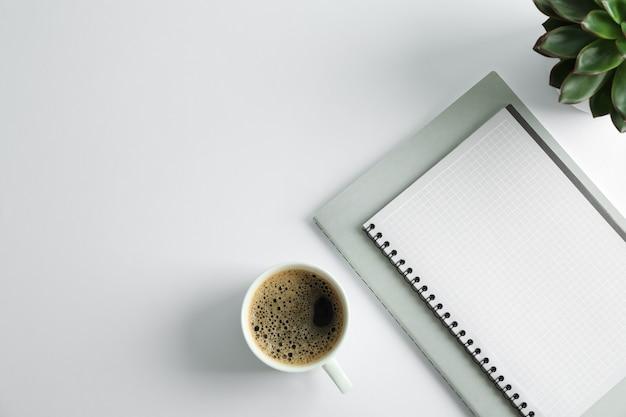 Quaderni, tazza di caffè e spazio per piante succulente per il testo