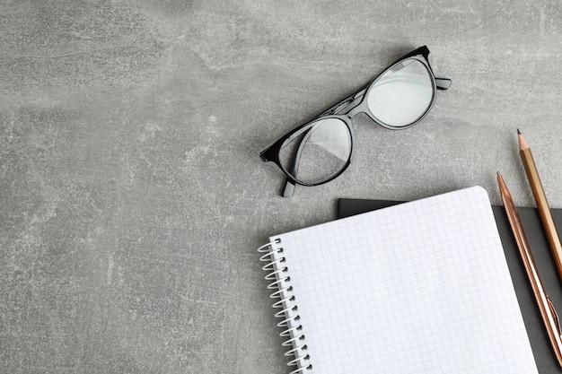 Quaderni, bicchieri e matita sul tavolo grigio, spazio per il testo