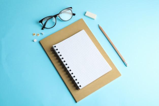 Quaderni, matita e bicchieri sullo spazio colore, spazio per il testo
