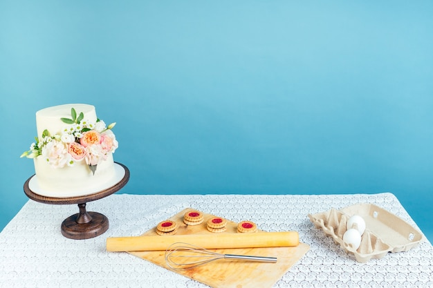 Copyspace mockup spazio di lavoro panettiere pasticcere pasticcere cremoso bianco torta nuziale a due livelli con fiori freschi sul tavolo e biscotti in studio su sfondo blu
