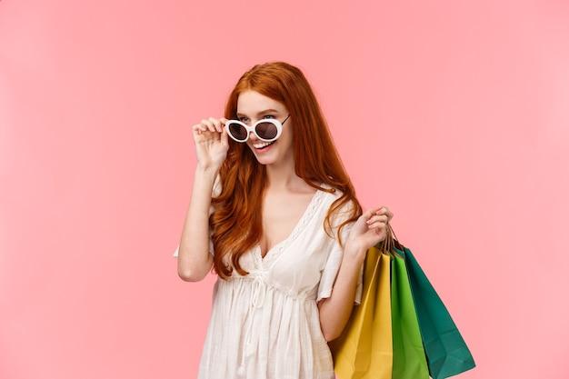 Civettuola e sicura di sé, donna rossa impertinente sullo shopping, controllando qualcosa di interessante, guardando da sotto gli occhiali, portare borse con merci, fare acquisti durante la stagione degli sconti, sfondo rosa