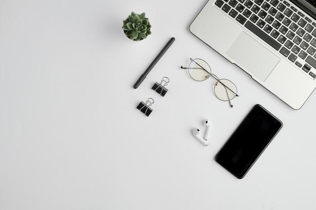 Auricolari cordless, occhiali da vista, penna, clip, gadget mobile, piccola pianta domestica verde e laptop su uno spazio bianco